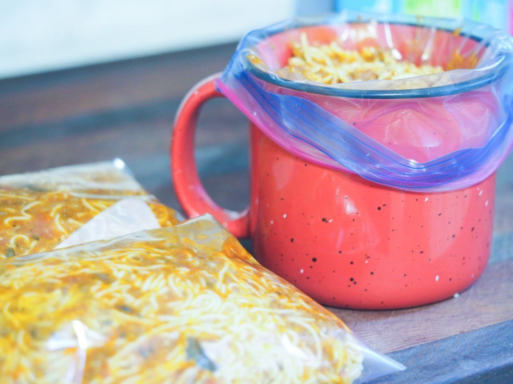 large red coffee cup with quart plastic bag inside filled with spaghetti to prepare for freezing.