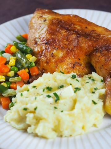 roasted leg quarter on white plate with mashed potatoes and mixed vegetables