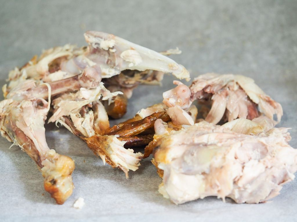 chicken bones on counter that have been cleaned with a little meat left on the bones