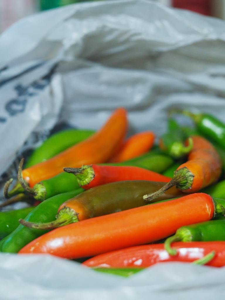 whole red and green serrano peppers in white plastic bag