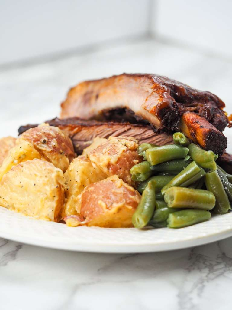 Plate with ribs, green beans,and cheesy potatoes