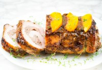 side view of stuffed pork loin stuffed with grilled peaches on white platter with fresh thyme garnish