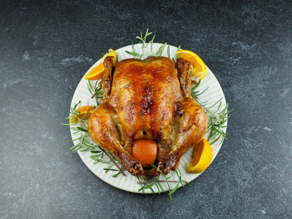 overhead view of roasted chicken on white plate with rosemary and orange sections on black counter top