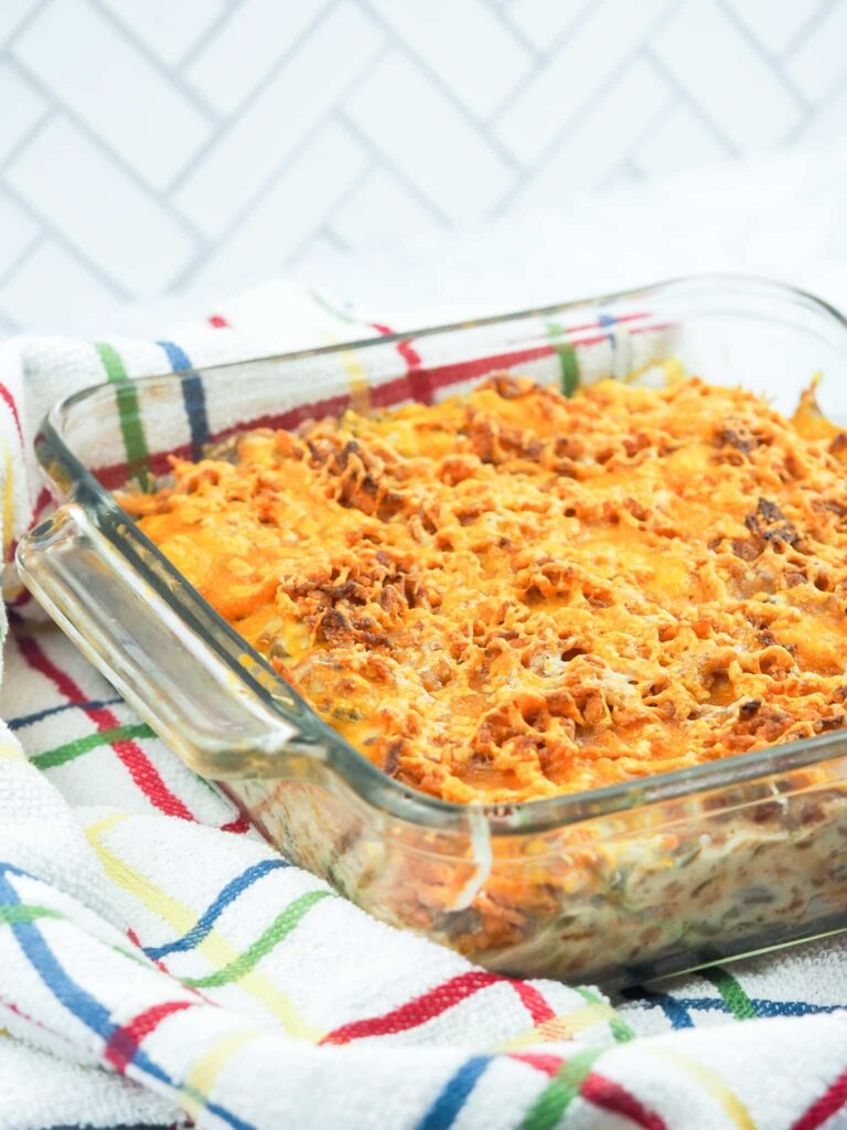 baked green bean casserole in glass baking dish on multi colored towel