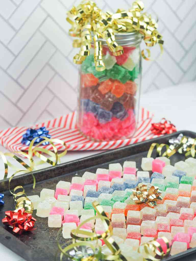 hard tack candy arranged in a mosaic pattern on a baking sheet with Christmas bows and ribbons with a jar in the top right background