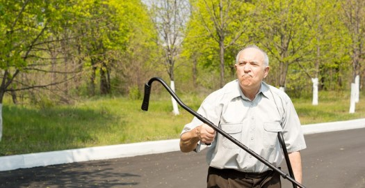 Grandparents standing in a rural street bordered by woodland waving his crutch in the air