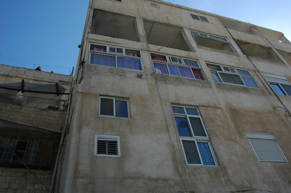 Blown out windows of the apartment of Abdel Rahman al-Shaludi. (Photo: Allison Deger)