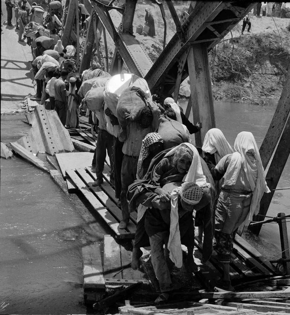 In this 1967 photo from the U.N. Relief and Works Agency, UNRWA, archive, Palestine refugees flee across over the Jordan river on the damaged Allenby Bridge during the 1967 Arab-Israeli war.