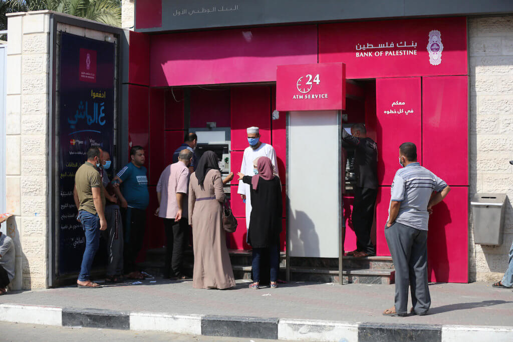 Palestinian Authority employees wear face masks as they wait to receive their salaries from a Palestine Bank ATM in the central Gaza Strip, September 1, 2020. (Photo: Ashraf Amra)