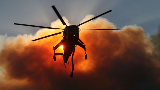 A firefighting helicopter pumps water during the Magic Fire.