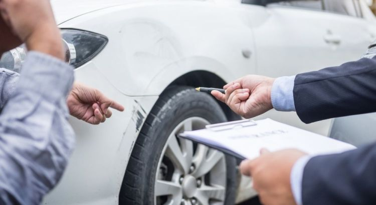 insurance agent examining car damage