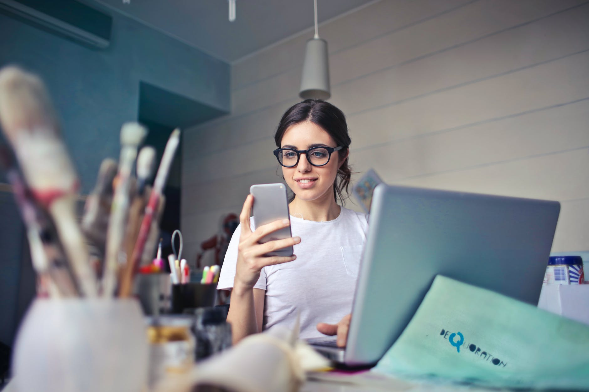 woman in white t shirt holding smartphone in front of laptop