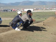 Mongolians squatting by road