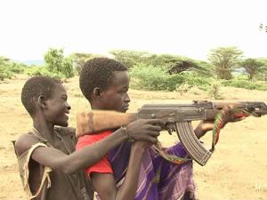 Lorunye training a friend on how to use an AK 47 riffle