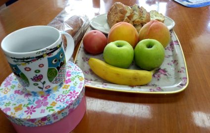 productivity hack treats image of wood table that has a tray of fruit including three peaches, two green apples, and a banana. Behind the tray is a place of sliced pastry bread. In the front to the left is a coffee mug with an owl design.