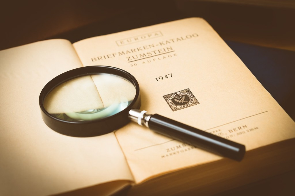 Necessary Preorders: magnifying glass on old book