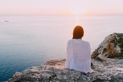 Frau sitzt auf Felsen und schaut aufs Meer