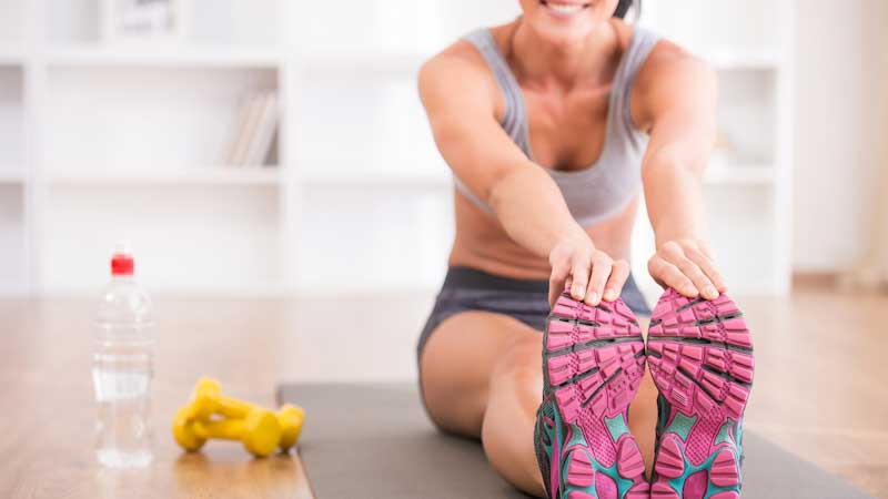 Fitness lady holding her feet, dumbbells
