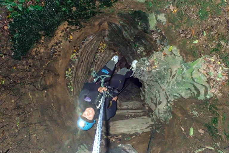 Girl abseiling into dark cavern in the Waitomo Glow Worm caves, New Zealand