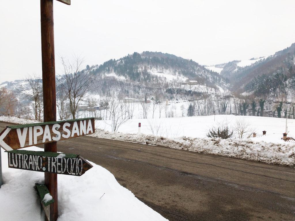 """un paesaggio innevato, sulla sinistra indicazioni stradali in legno: """"vipassana"""""""