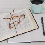 An open Bible laying on top of a notebook with pen. There is a pair of glasses sitting on top of the Bible, and a mug of coffee beside it.