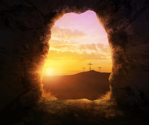 three crosses in the distance as seen through an open tomb door, with the sun rising