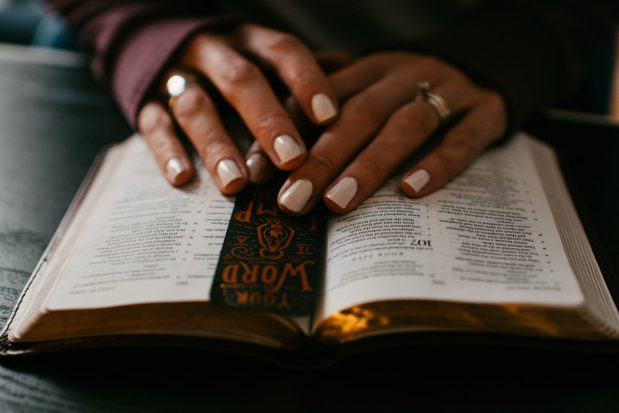An opn Bible on a lady's lap, with a black leather bookmark and her hands placed upon it