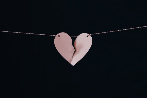 a pink paper heart hung up on string and broken down the middle