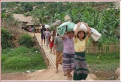 Refugee women carry home their rations in Ban Don Yang refugee camp ( Photo: UNHCR / K. McKinsey / 2 May 2007 )