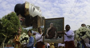 Sitting Sayadaw is carried by two devotees as the parade passes by the well-known Reclining Buddha statue [seen in the back] (Photo: Jaeneh Aong/MNA)