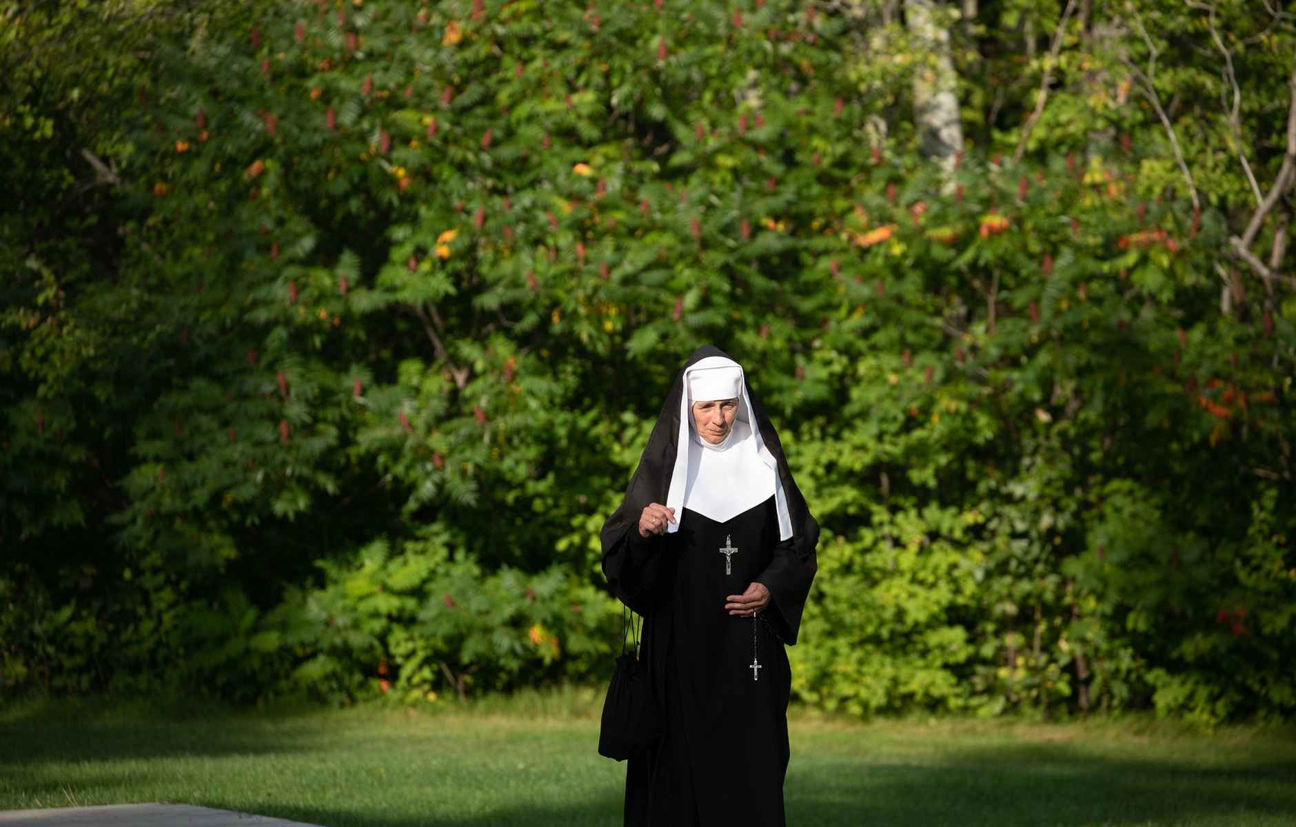 nun walking near trees