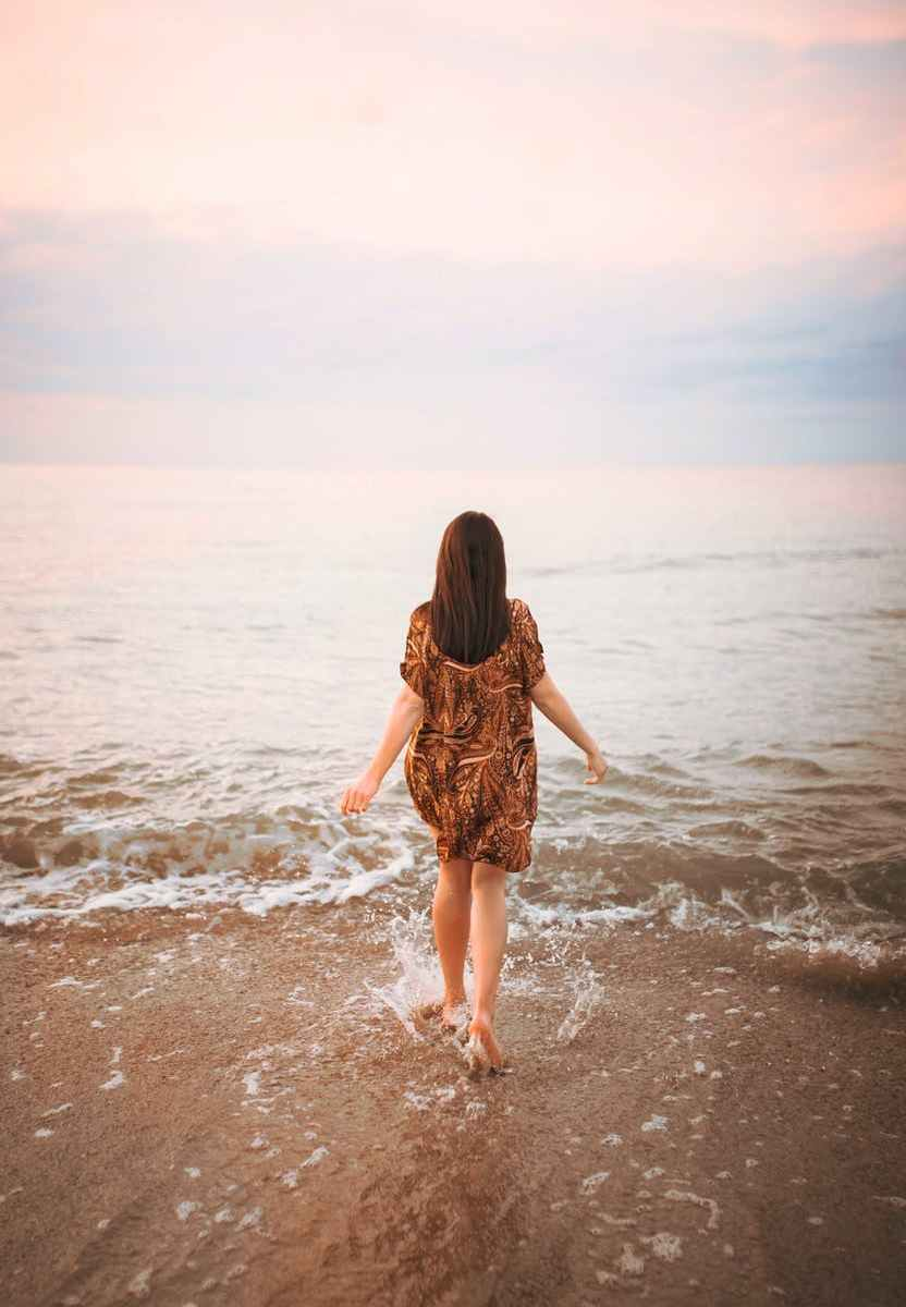 anonymous woman walking on beach towards sea waves