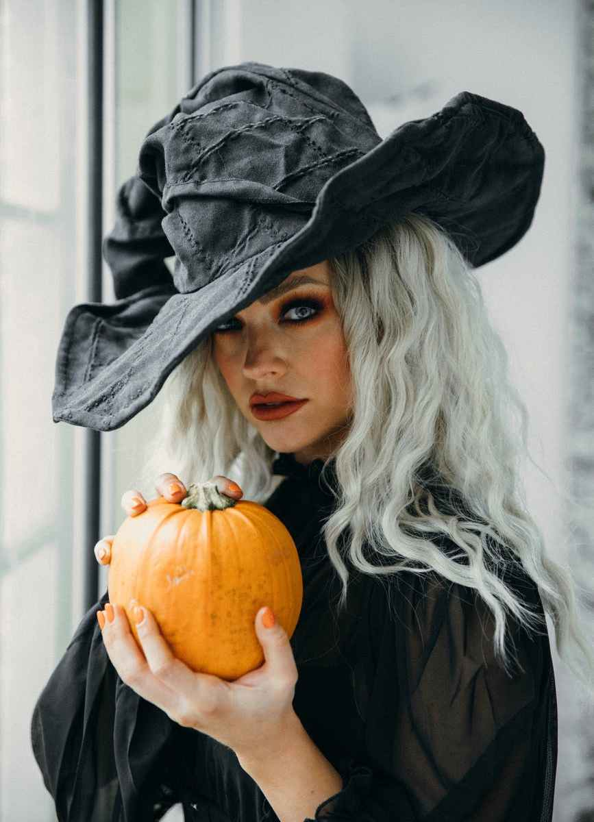 woman in black witch hat and dress while holding a halloween pumpkin