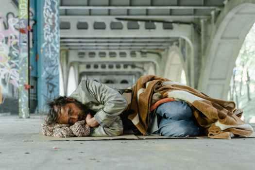 man in brown jacket lying on floor