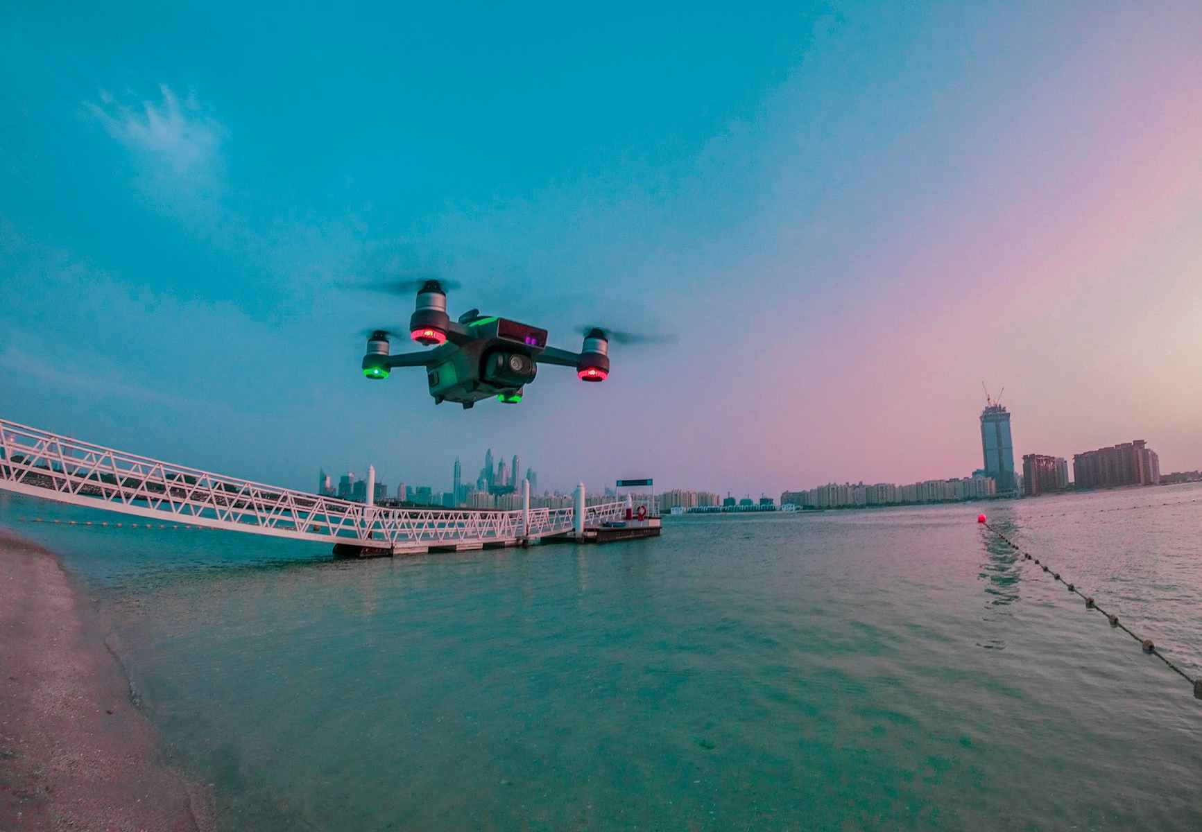 modern drone filming video while flying above city river