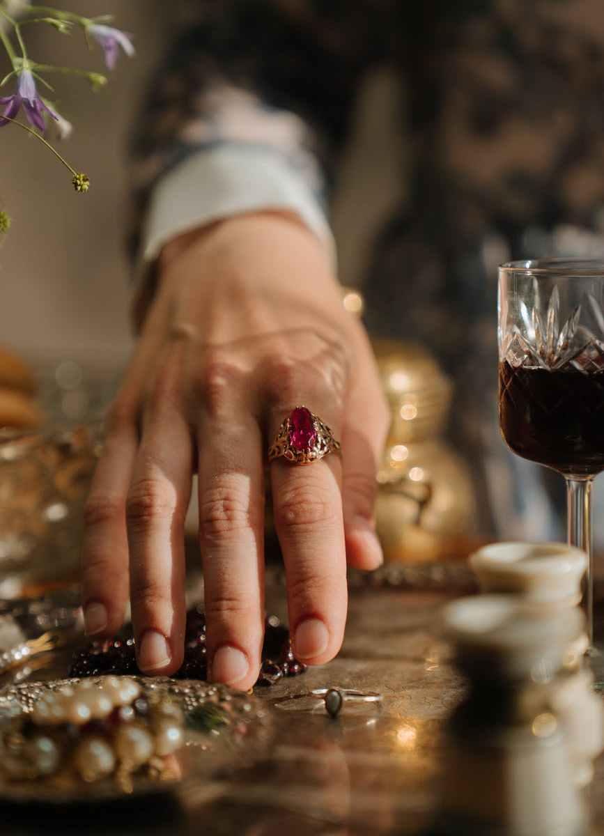 person wearing silver ring and red and gold ring