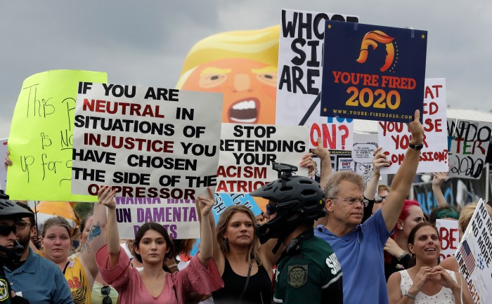 Protestors hold up anti President Donald Trump signs during a rally Tuesday, June 18, 2019, in Orlando, Fla.