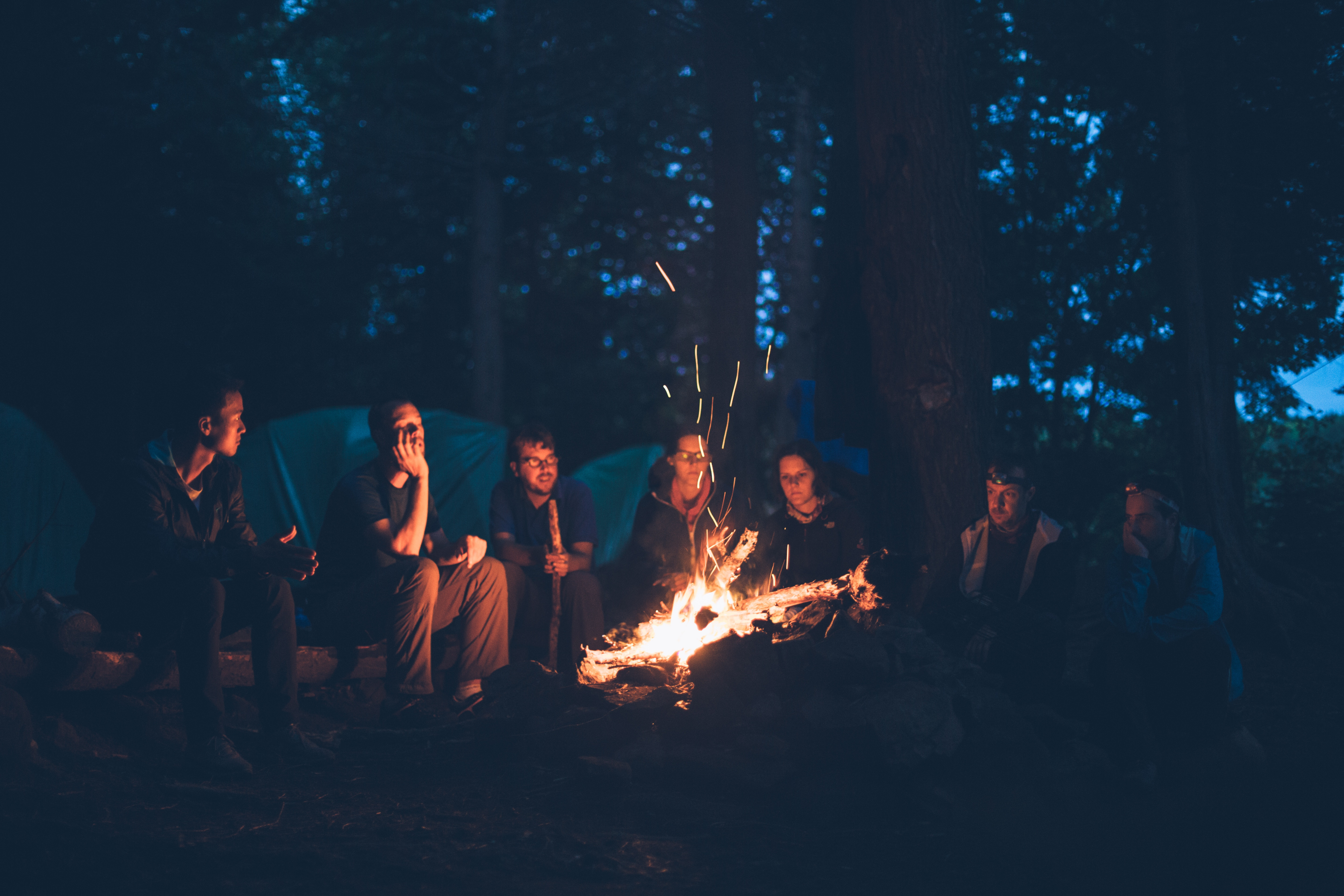 A group of people, laughing around a campfire