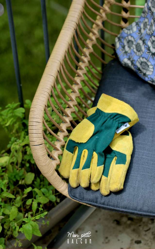 gants de jardin vert et jaune posé sur fauteuil de jardin en rotin