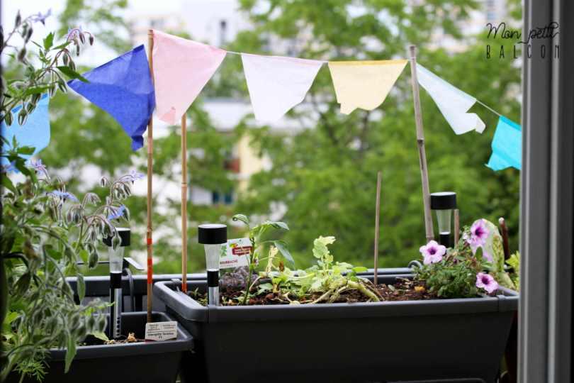 guirlande multicoloe en papier planté dans des jardinières grises, décoration d'un petit balcon, HEMA