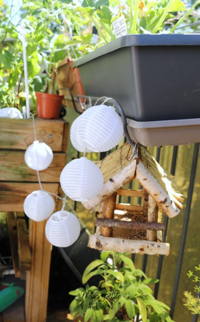 guirlande lumineuse LED façon guinguette boule blanche accrochée au balcon