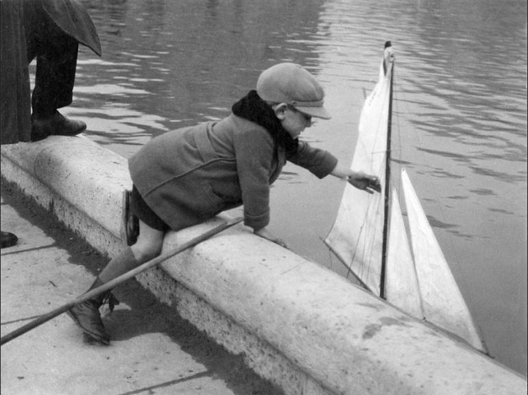 Enfant jouant avec sa péniche dans le bassin du Luxembourg