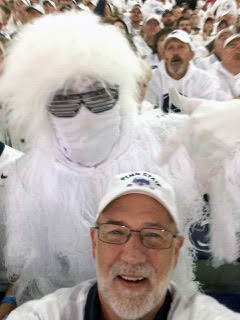 Man in white Penn State hat takes selfie with a white costumed Penn State fan