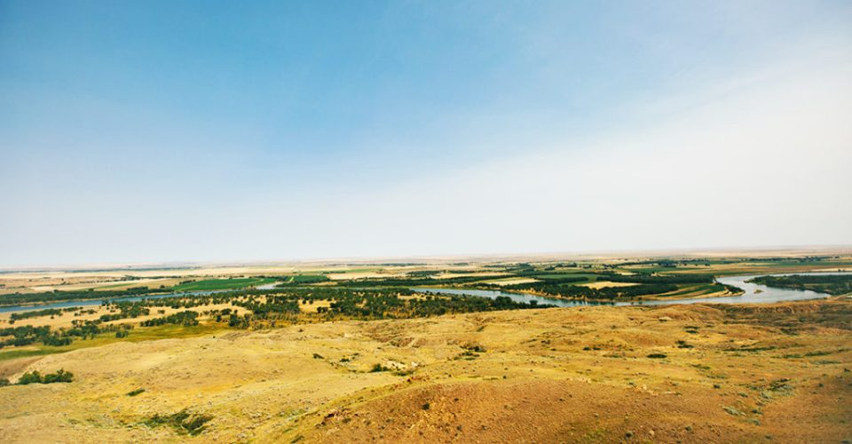 A broad landscape of prairie grass rolls toward the green floodplain of the Missouri River near its confluence with the Milk River. The Milk and Missouri Rivers make up portions of the Fort Peck Indian Reservation boundary.