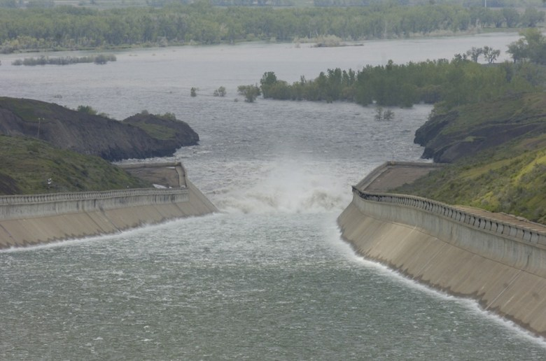Water crashes into a bay at the end of a long, concrete spillway at the bottom of the Fort Peck Dam.