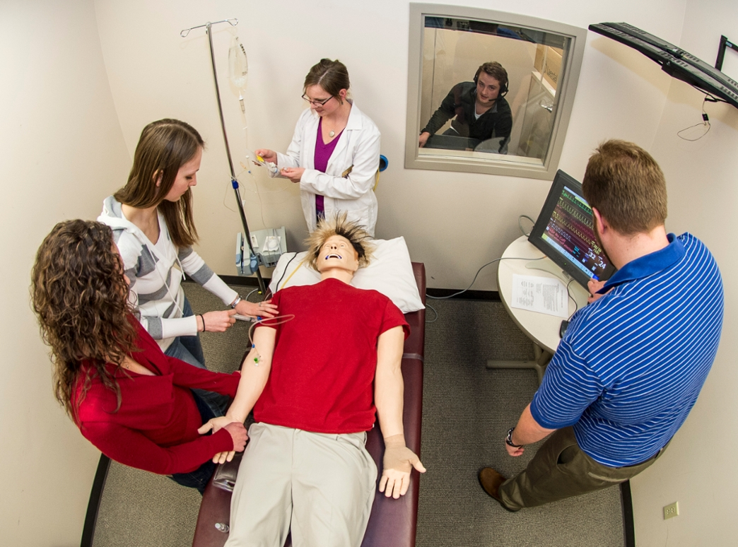 "A group of pharmacy students in an elective course work on ""Sim Man,"" a computerized dummy that tests students by being programmed with different health scenarios."