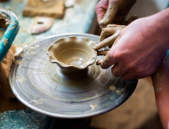 Mentor helps child with pottery