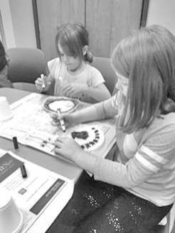 Peyton Cardwell of Blacksburg, left, and Annabelle Glassbrenner of Christiansburg work on their coffee filter circles, making them colorful with dots. The seven-year-olds were participating in Christiansburg Librray's November Art Club.