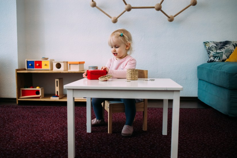 toddler doing coinbox material work at montessori table in class