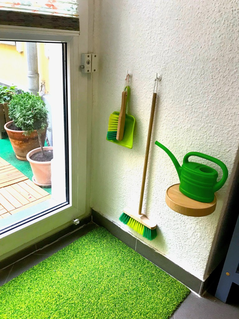 montessori sweeping watering can green garden work on wall hooks prepared in the montessori care of the outdoor environment in nature farm to table little ikea wall shelf
